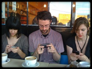 three people looking at websites on their mobile phones